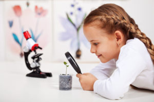 photo of a young girl looking at a plant through a magnifying glass